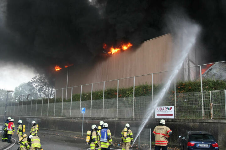 Feuerwehrleute löschen eine Gewerbehalle, in der Elektroschrott in Brand geraten ist.
