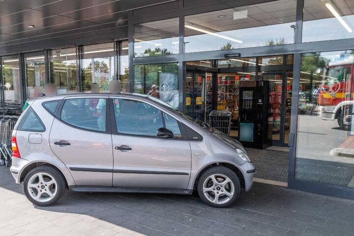 Das Auto steht vor dem Eingang eines Supermarktes.