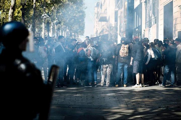 Demonstranten wenden sich ab, aus Schutz vor Tränengas, das von Bereitschaftspolizisten abgefeuert wurde.