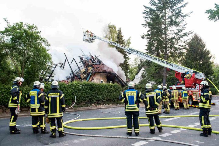 Feuerwehrleute stehen vor dem zerstörten Wohnhaus, aus dem dicker Rauch aufsteigt.