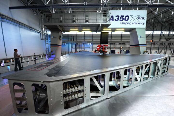 Mit über 32 Metern Länge sind die Tragflächen das größte Bauteil des Airbus A350. Der wird im niedersächsischen Stade montiert, wobei ein Tapeleger (kl.F.) Kohlefaser auf die oberste Flügelschale aufbringt.
