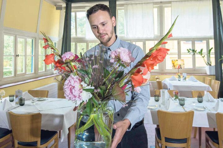 Christian Meinhold (27) dekoriert das Restaurant Villa Esche mit einem  frischen Blumenstrauß.