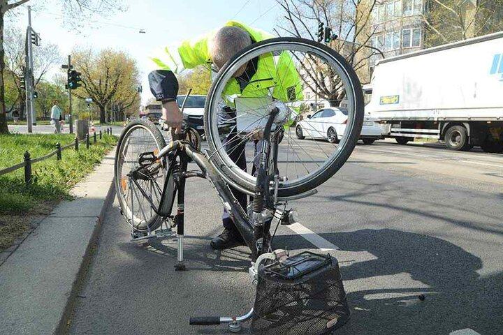 Der Polizist untersucht das verunfallte Fahrrad.