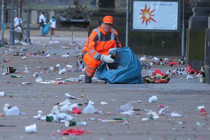 Größerer Müll wie Sektflaschen, Böller-Batterien oder Raketenstangen müssen mit den Händen eingesammelt werden, bevor die Kehrmaschine ran darf.
