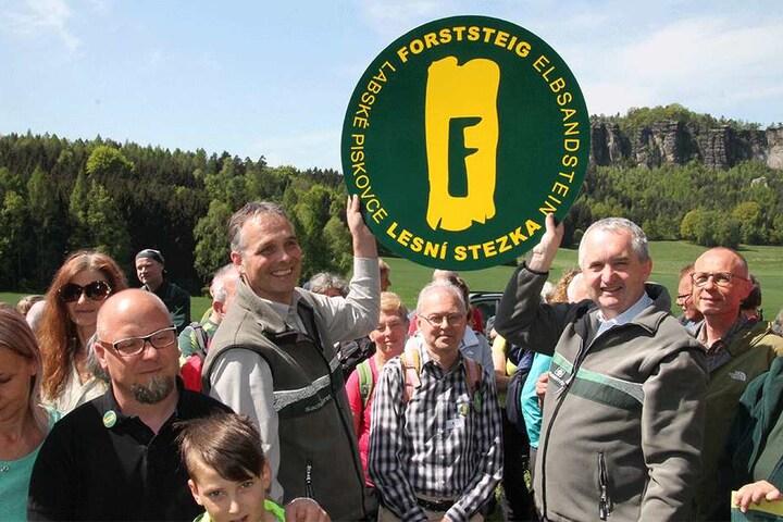 """Umweltminister Thomas Schmidt und Uwe Borrmeister, Leiter des Forstbezirkes Neustadt halten stolz ein XXL-Logo vom """"Forststeig Elbsandstein"""" in die Höhe."""