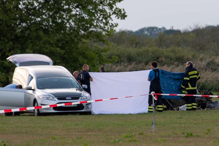Die Leiche des tödlich verunglückten Piloten wird nach dem Absturz von einem Kleinflugzeug auf einem Feld zwischen dem Ortsteil Badingen und Gransee in eine Bestattungswagen verladen.