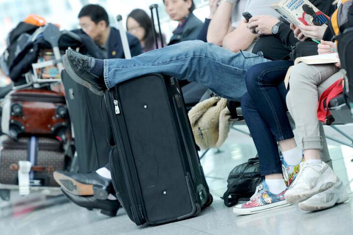 Passagiere warten am Flughafen mit ihrem Gepäck. Wer kein Auge auf seinen Koffer hat, hat schnell das Nachsehen, wie die Polizei nun berichtete. (Archivbild)