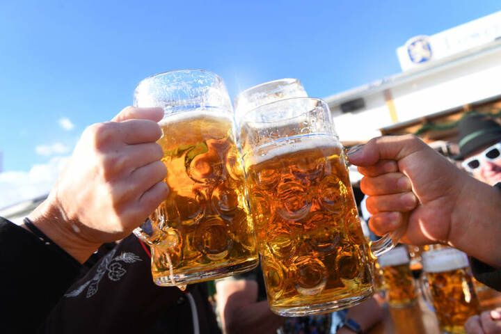 Besucher stoßen auf dem Oktoberfest mit Maßkrügen voller Bier an.