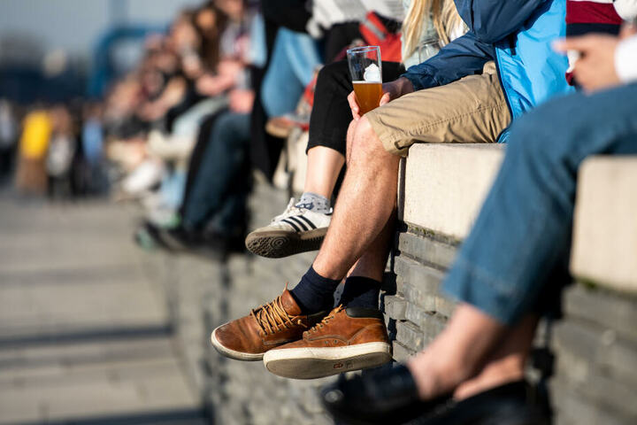 Menschen sitzen auf einer Mauer am Rheinboulevard und genießen die Sonne
