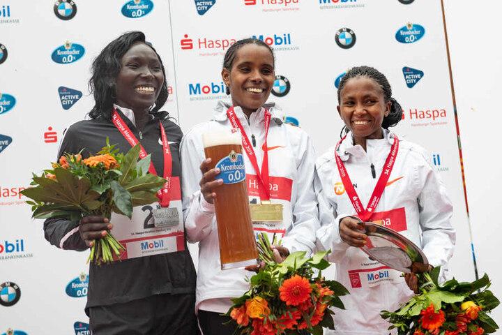 Marathon-Siegerin Dibabe Kuma (Mitte) aus Äthiopien, die zweitplatzierte Magdalyne Masai (l) aus Kenia und die drittplatzierte Failuna Matanga aus Tansania jubeln beim 34. Hamburg Marathon bei der Siegerehrung.