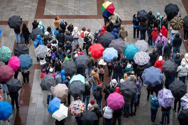 Touristen mit Regenschirmen auf dem Marienplatz in München. Am an diesem Wochenende sollte die Kleidung wetterfest sein.