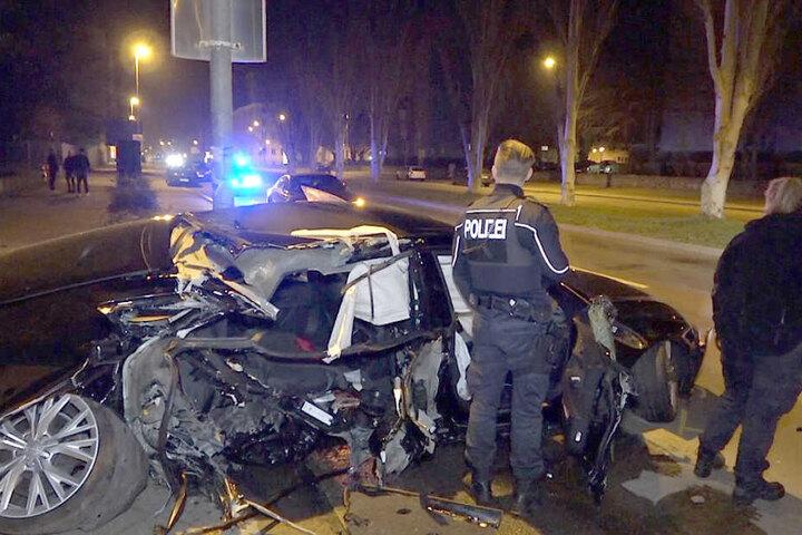 Autorennen auch in Magdeburg? Polizisten stehen an einem völlig demolierten Auto. Nach dem Verkehrsunfall ermittelt die Polizei, ob es möglicherweise vorher ein illegales Autorennen gegeben hat.