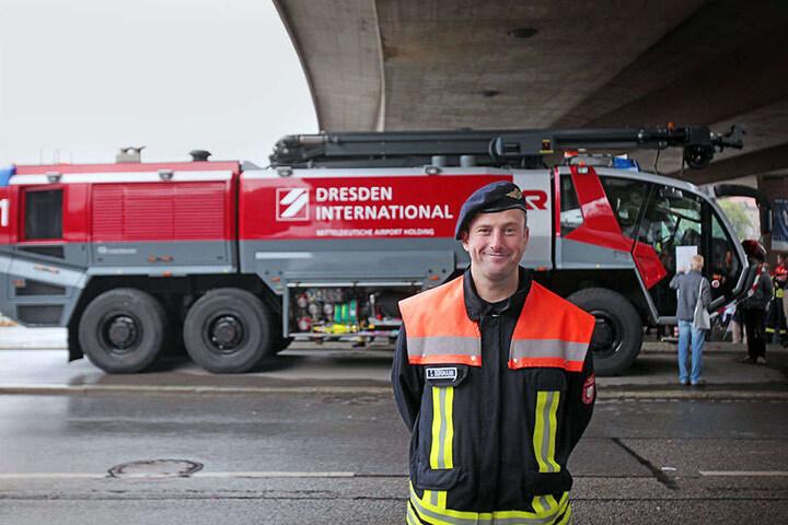 """Zufrieden mit dem Besucherandrang: Sandro Bergmann (38) von der Flughafen-Feuerwehr vor dem modernen Löschfahrzeug """"Panther 3"""" unter der Carolabrücke-"""