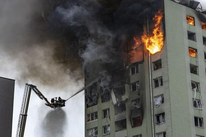 Feuerwehrleute löschen auf einer Drehleiter einen Brand in einem 12-stöckigen Mehrfamilienhaus, das durch eine Gasexplosion schwer beschädigt wurde.