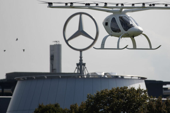 Ein sogenannter Volocopter fliegt in Stuttgart vor einem Gebäude des Autobauers Daimler.