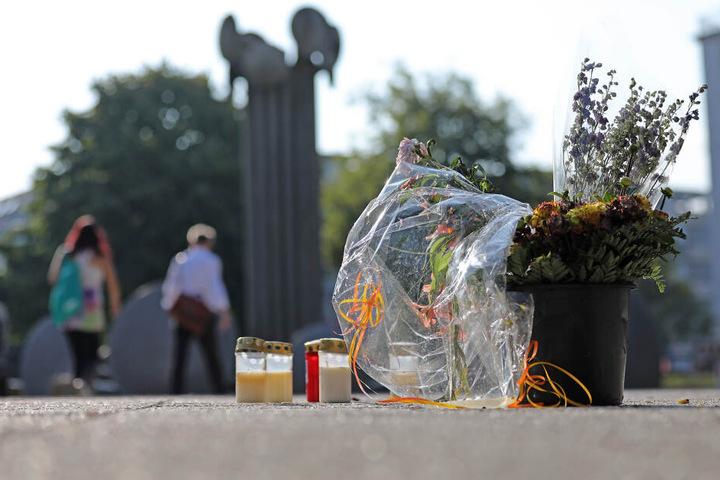 Blumen und Kerzen stehen am Tatort auf dem Ebertplatz.
