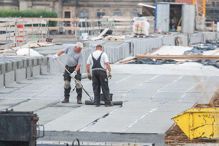Damit die Brücke künftig dicht bleibt: Arbeiter tragen die neue Bitumenschicht auf.