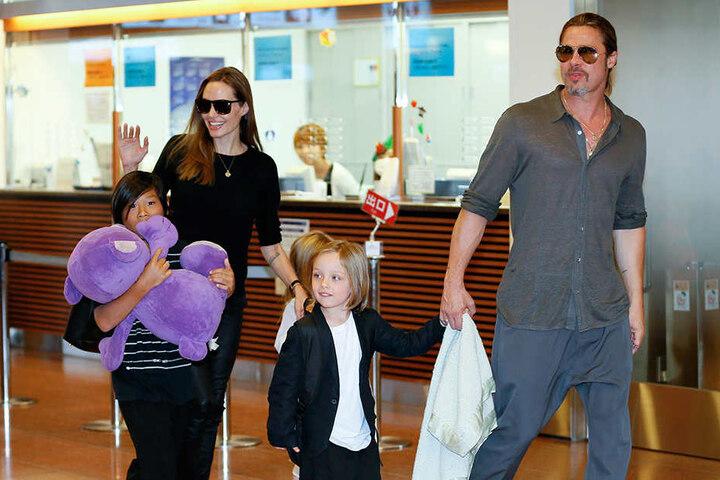 Die US-Schauspielerin Angelina Jolie und ihr Mann Brad Pitt kommen mit ihren Kindern Pax Thien (li), Shiloh (verdeckt) und Knox Jolie-Pitt im Juli 2013 in Tokyo am Internationalen Flughafen Haneda an.