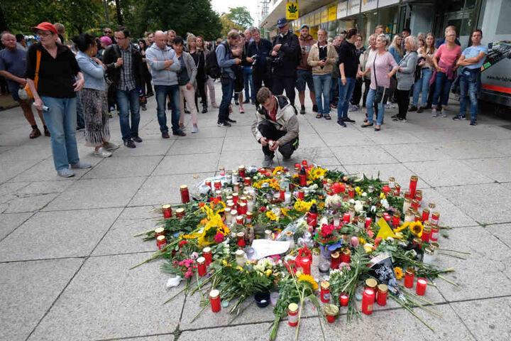 Blumen und Kerzen stehen bzw. liegen am Tatort in der Innenstadt.