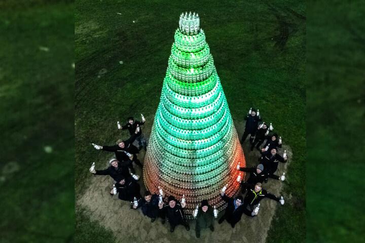 """Bauhelfer aus Bendorf-Oersdorf stehen vor ihrer """"Schnapsidee"""", einem Tannenbaum aus 5038 leeren Kornflaschen."""