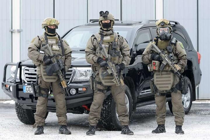 Polizisten stehen vor einem der gepanzerten Toyota Land Cruiser V8.