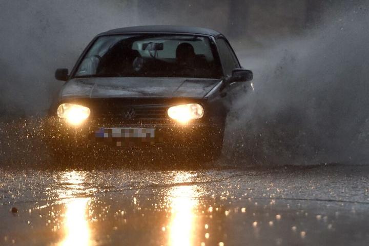 Ein Auto fährt über eine überschwemmte Straße.