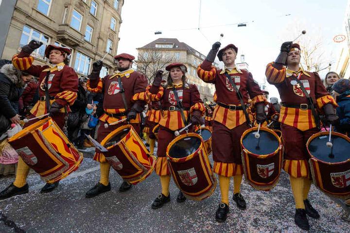 Musiker in Kostümen nehmen am großem Faschingsumzug durch die Innenstadt teil.