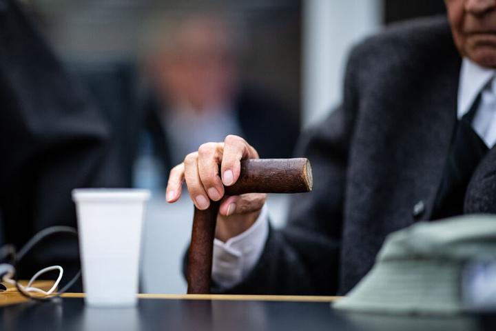 Zu Beginn des Prozesses gegen einen ehemaligen SS-Mann sitzt der Angeklagte im Landgericht auf der Anklagebank und hält mit seiner Hand seinen Gehstock fest. Das Landgericht Münster hat das Verfahren gegen einen ehemaligen SS-Wachmann im Konzentrationslag