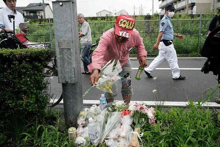 Ein Mann legt Blumen für die Opfer des Anschlags im Studio der Kyoto Animation Co. nieder.