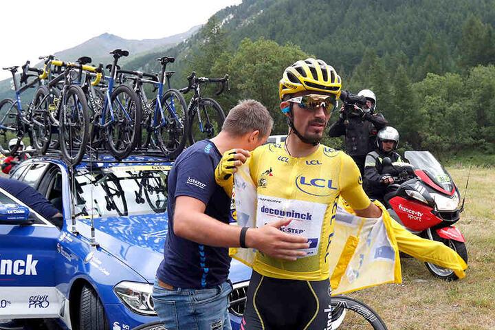 Julian Alaphilippe aus Frankreich vom Team Deceuninck-Quick-Step im gelben Trikot zieht sich vor dem Teamwagen eine Jacke an