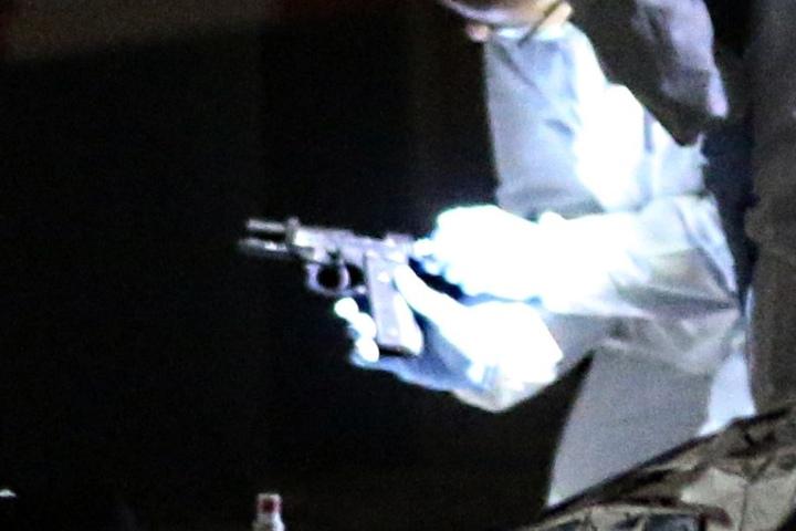 Ein Ermittler begutachtet am Tatort eine Waffe. Ist es das Tatwerkzeug?