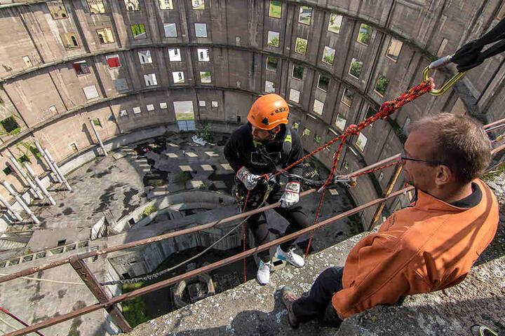 Ein imposanter Blick hinunter: Patrick Wiegers (l.) lässt sich in 43 Metern Höhe die ersten Schritte hinab am Seil von Vertikalis-Geschäftsführer Lars Thielsch erklären.