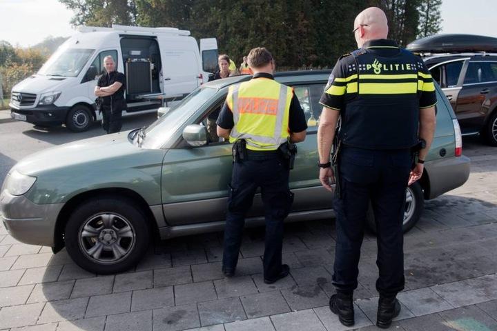 Polizisten aus den Niederlanden und Deutschland kontrollieren ein Auto bei einer Großkontrolle.