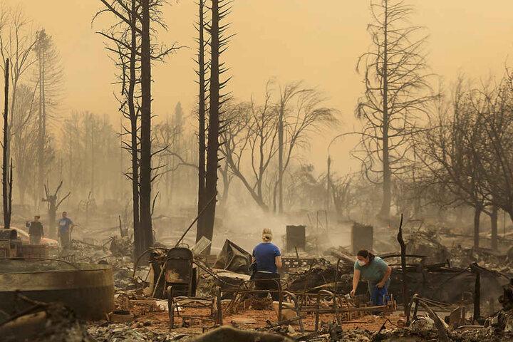 Anwohner durchsuchen die Überreste eines abgebrannten Gebäudes.