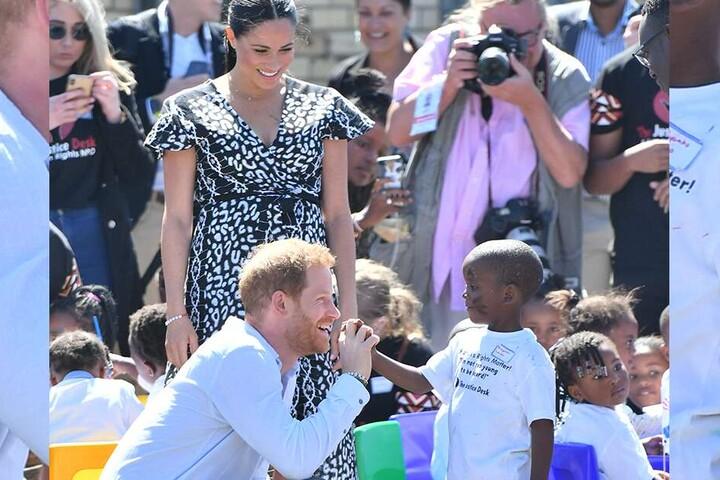 Prinz Harry begrüßt einen kleinen Jungen in der Gemeinde Nyanga.