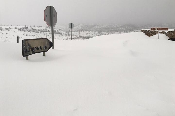 Ein Schild, das die Distanz zum Dorf Vallibona anzeigt, ist fast komplett mit Schnee bedeckt.
