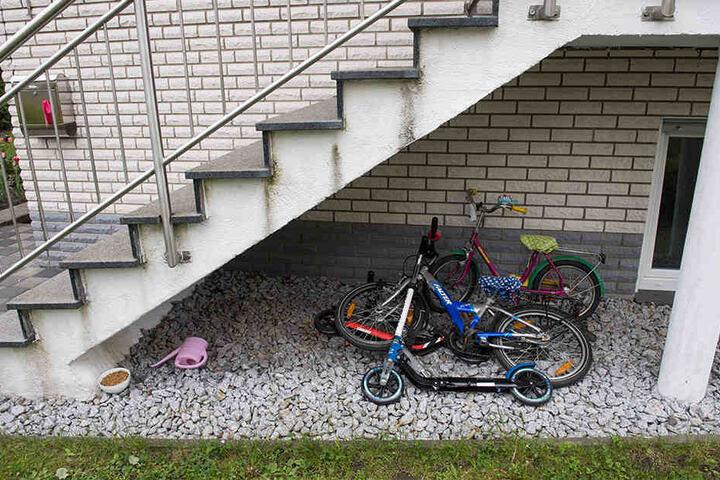 Kinderfahrräder und ein Tretroller liegen unter der Treppe des Hauses.