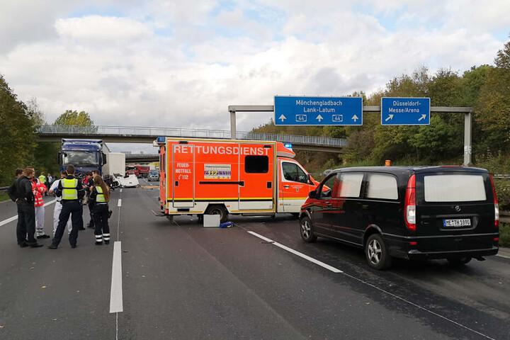 Polizisten und Rettungskräfte stehen neben einem Krankenwagen und einem Leichenwagen auf einer Fahrbahn der Autobahn A44 in Düsseldorf.