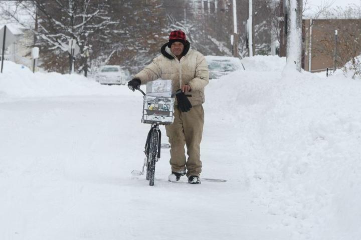 Logan Rogers schiebt in Erie, Pennsylvania, USA, sein Fahrrad durch den Schnee.