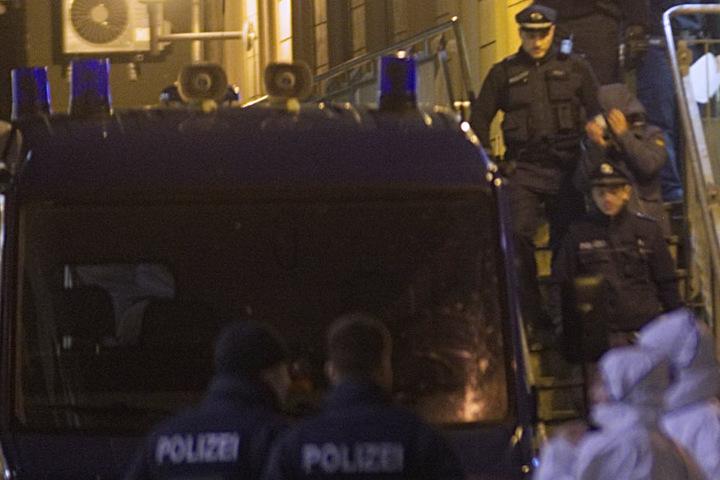 Ein mutmaßlicher Täter wird von der Polizei abgeführt.