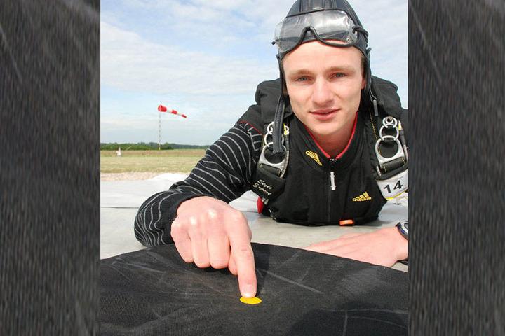 Nationalmanschaftsspringer Jan Herre zeigt den nur drei Zentimeter kleinen  Punkt, den man beim Zielspringen treffen muss.