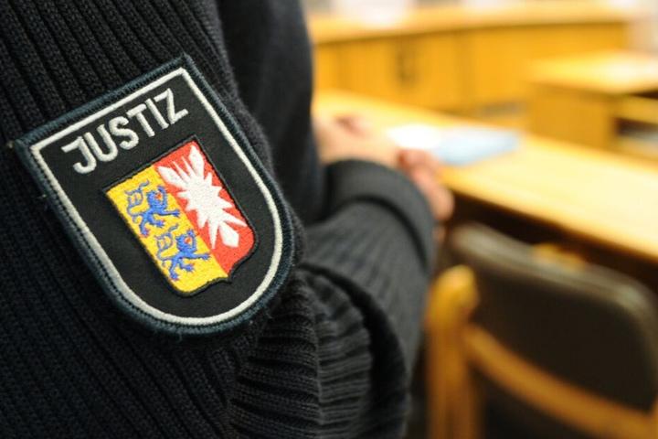 Ein schleswig-holsteinischer Justizbeamter steht im Landgericht im Sitzungssaal.