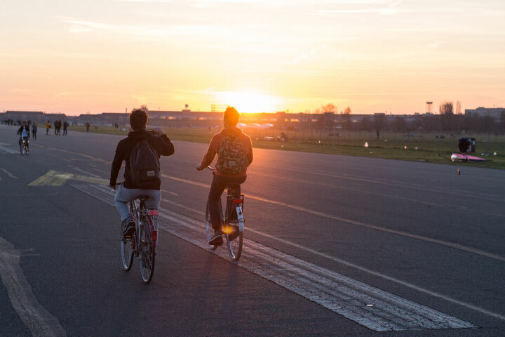 Bei untergehender Sonne und blauem Himmel zieht es immer wieder Radfahrer auf das Tempelhofer Feld.