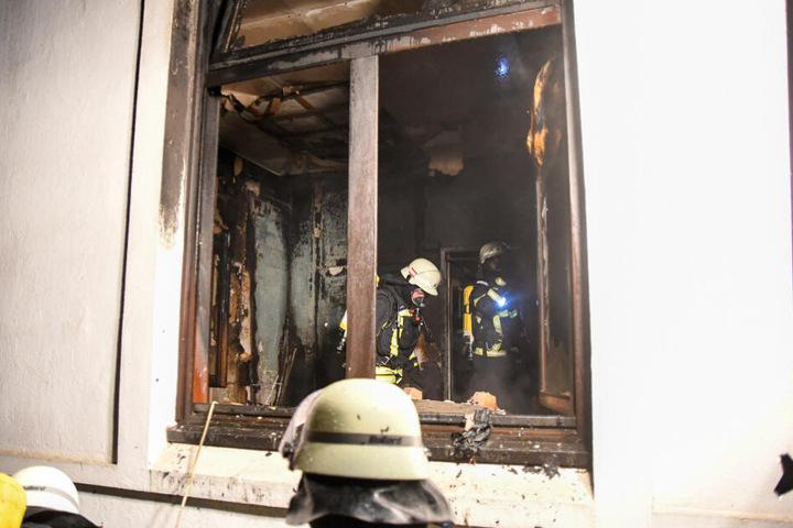 Einsatzkräfte durchsuchen das Zimmer nach Brandherden.