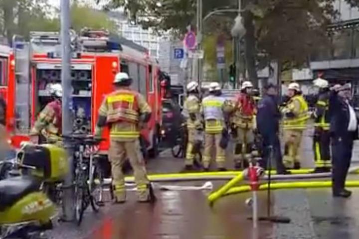 Feuerwehrmänner sind vor dem Europa-Center und tragen Ausrüstung ins Gebäude.