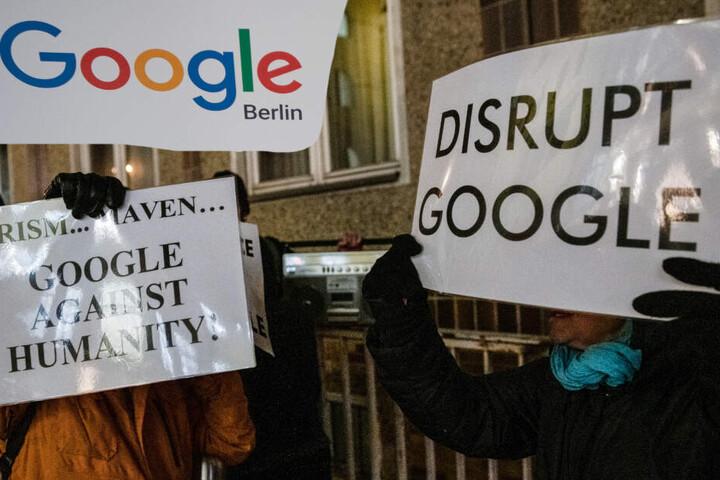 """Der Protest wurde mit lautstarker Musik unterlegt. """"Google gegen die Menschlichkeit"""" steht auf einem Plakat. (Bildmontage)"""