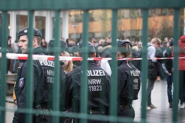 Polizisten stehen im Schulgelände, die Schüler haben das Gebäude verlassen.