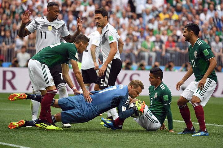 Manuel Neuer (MItte) begräbt die Kunstlederkugel nach einer Ecke unter sich.