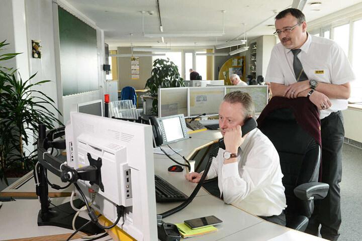 Gruppenleiter Jörg Pinter (47) schaut dem Diensthabenden Schichtleiter  Andreas Barth (53) in der Leitstelle über die Schulter.
