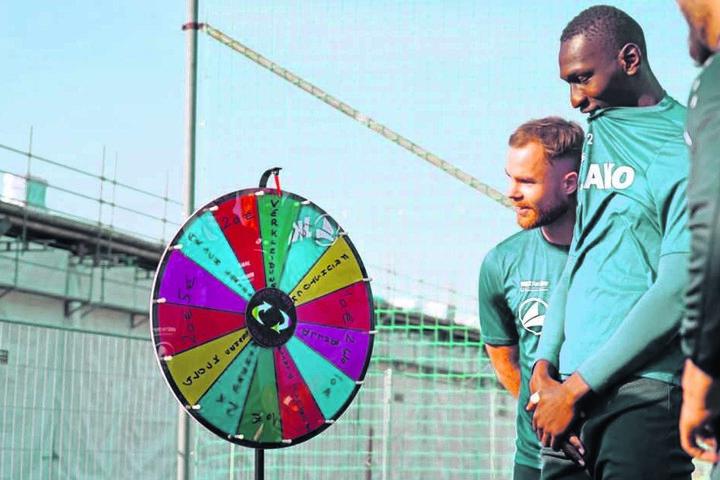 Tobias Müller und Tarsis Bonga (r.) blicken gespannt auf das Glücksrad. Das brachte Chefcoach Patrick Glöckner in der Vorwoche erstmals mit auf den Trainingsplatz.